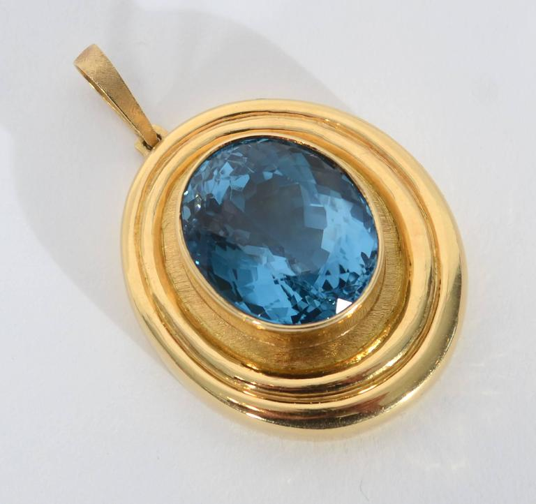 Stunning oval pendant by famed Brazilian brothers, Roberto and Haroldo Burl Marx. The central blue topaz weighs 37 karats.It is set in a glossy bezel surrounded by a slightly burnished oval. Outside that are two glossy ribbed frames. The variation