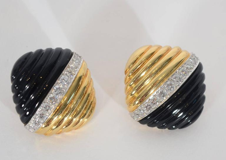 Striking earrings by Trianon with half in ribbed gold and the other half mirroring the ribbed pattern with carved onyx. Separating the two materials is a row of VS 1 diamonds weighing a total of approximately 2.2 carats. Backs are clips. A  design