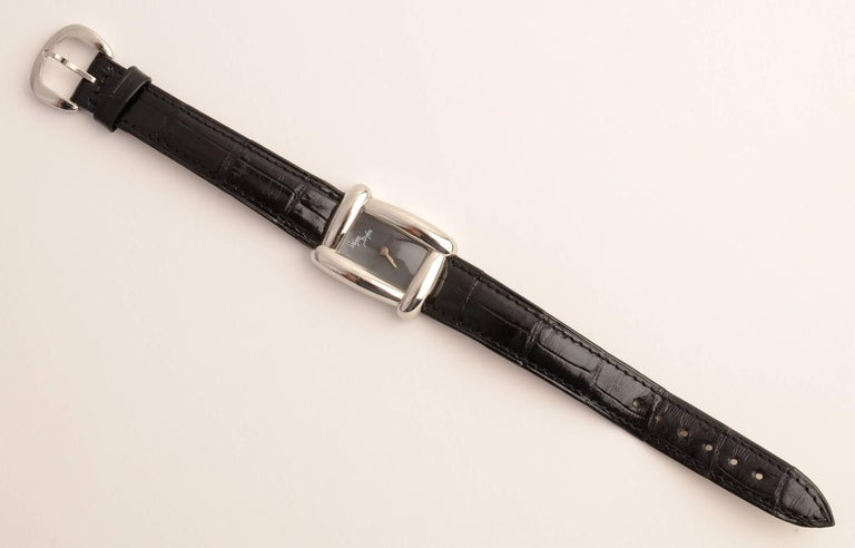Stylish wrist watch by American jewelry designer, Henry Dunay. The rectangular black face is framed by the curvilinear design characteristic of his watches. Black leather band is original.