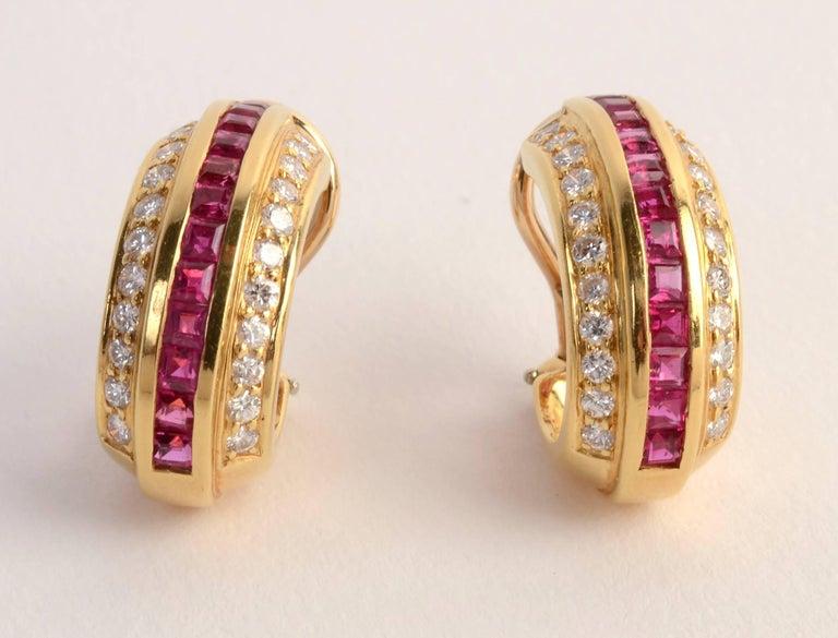 Elegant ruby and diamond oval hoop earrings by Cartier. There are 44 round diamonds weighing a total of .88 carats. Backs are posts and clips. Measurements are 3/4 inch in length and 3/8 inch  in width.