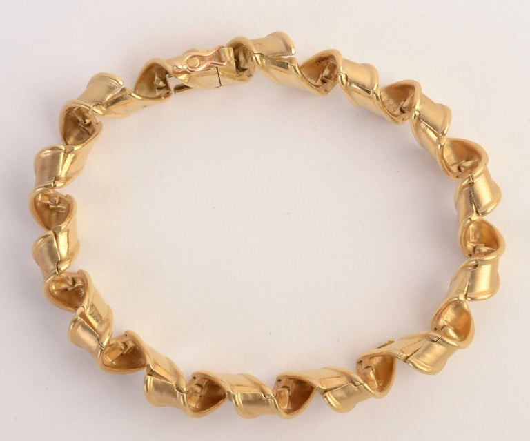 Graceful Tiffany bracelet in which the gold links effectively look like curled ribbon. Each link has two hinges to allow this to occur. The bracelet is 7 1/2 inches in length and half an inch in width. Made in France; circa 1960's.