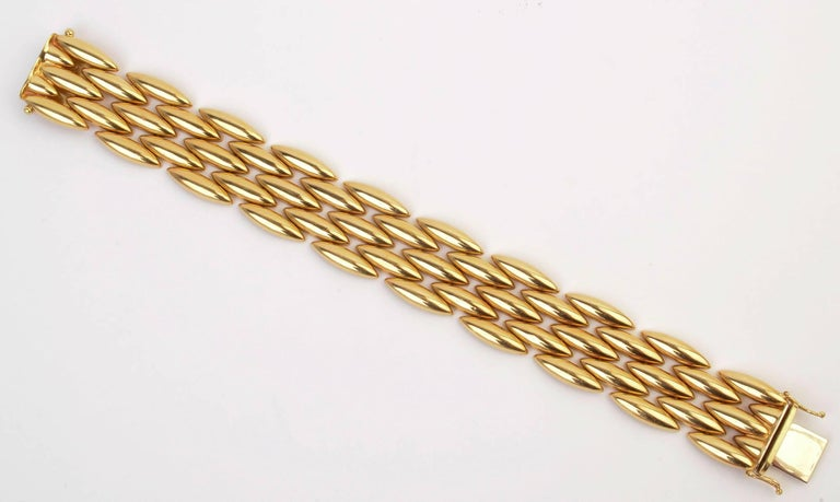 "Classic eighteen karat gold bracelet by Cartier with five rows of navette shaped links. The matching necklace is offered as item LU1333250523. Both are an especially rich shade of gold. The bracelet is 3/4"" wide and 7 5/16"" long."
