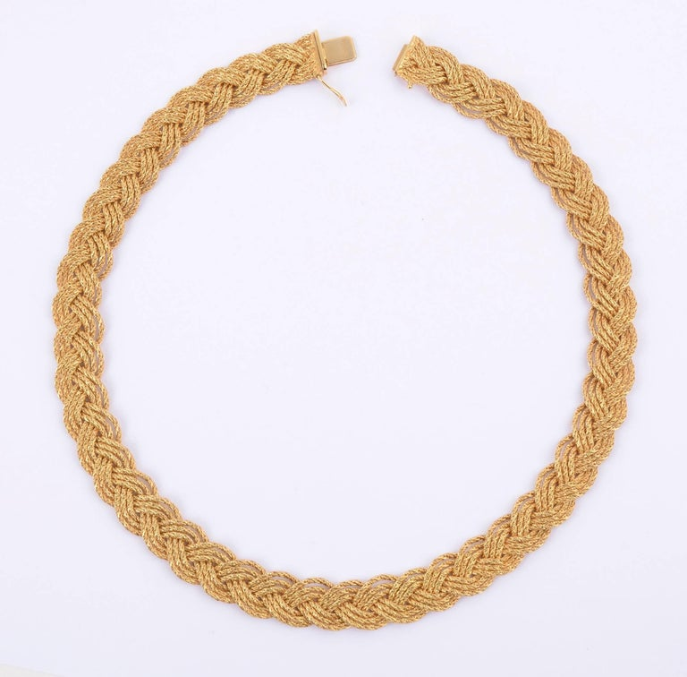 Beautiful eighteen karat gold choker necklace by Tiffany and Co. It is made of three braided strands of gold. Each strand is made  with a herringbone weave. The complexity of the braiding with the herringbone gives a wonderful glimmer to the