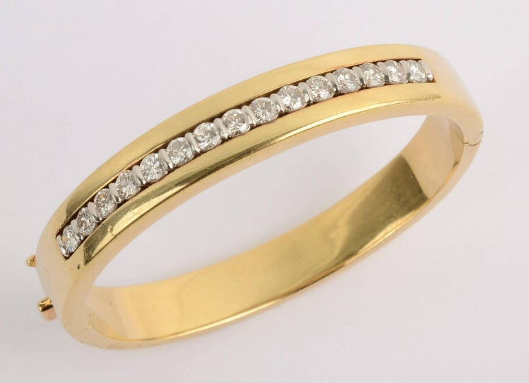 Eighteen karat gold hinged bangle bracelet by Tiffany with diamonds set in platinum. The bracelet has 15 diamonds that weigh a total of 2.25 carats. The bracelet is very secure with a good safety clasp. The interior measures 2 1/8 inches fitting a