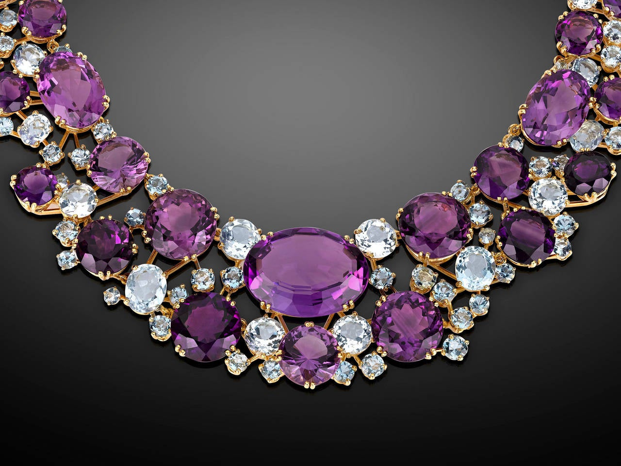 A breathtaking array of amethysts and aquamarines cascade around the neck in this timeless necklace by Verdura. Beautifully hued oval and circular-cut amethysts of graduated size rest amongst shimmering blue aquamarines that perfectly accentuate the