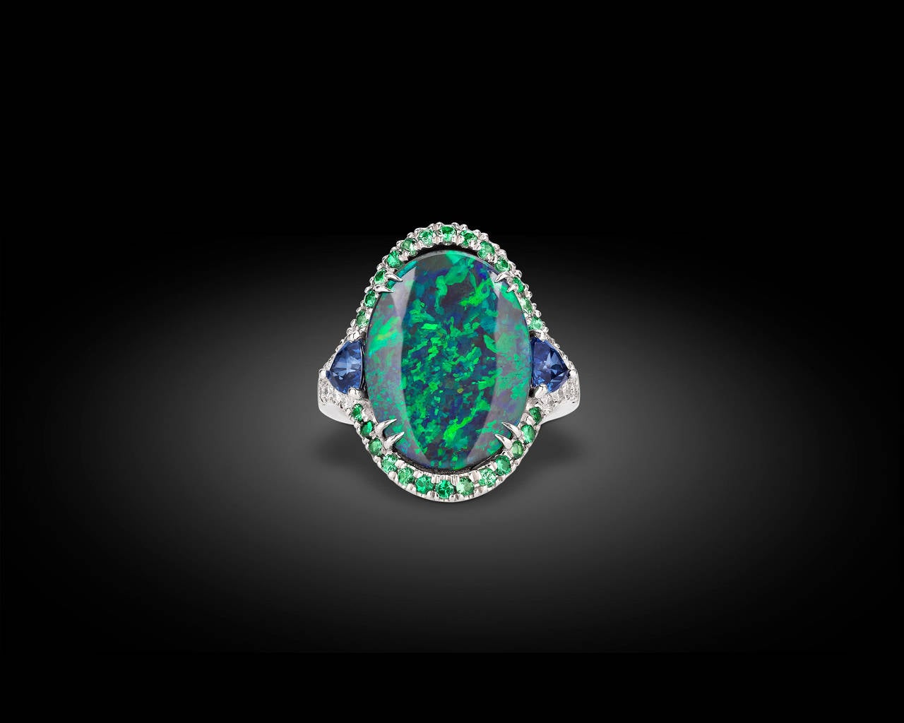 A vision of kaleidoscopic color, this extremely rare Lightning Ridge black opal displays an impressive range of iridescent blue and green hues. The remarkable color of the 3.60-carat opal is perfectly accented by a halo of colored gemstones,