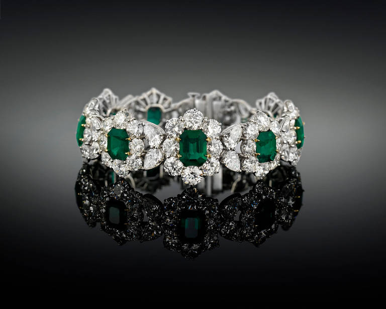 Nine perfectly-matched Colombian emeralds, each displaying the ideal emerald green hue, distinguish this magnificent bracelet. Totaling 14.16 carats and certified by C. Dunaigre to be Colombian in origin, these rare gems are nestled between 33.82