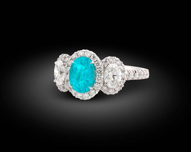 An exquisite 1.33-carat Paraiba tourmaline is showcased in this dazzling ring. Paraiba tourmalines are among the most exciting gemstones in the world, and this stone exhibits the signature neon blue-green color of only the finest specimens. This