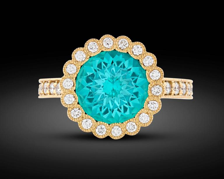 A dazzling 2.86-carat tourmaline is featured in this exquisite ring. Exhibiting a deep turquoise blue hue, the stunning gem is joined by approximately 0.51 carat of shimmering diamonds in its delicate 18k yellow gold setting.