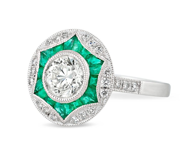The 0.92-carat round center diamond is boldly bordered by 0.47 total carat of lush green emeralds and 0.21 additional carat of glistening diamonds. This striking, structural setting allows these spectacular jewels to shine. Set in platinum.
