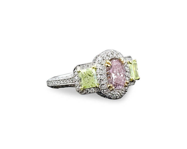 Colored diamonds are the rarest and most exquisite of nature's treasures. This ring showcases not one, but three natural fancy colored diamonds of brilliant color and shimmer. The center diamond is a stunning 1.08-carat pinkish-purple diamond, with