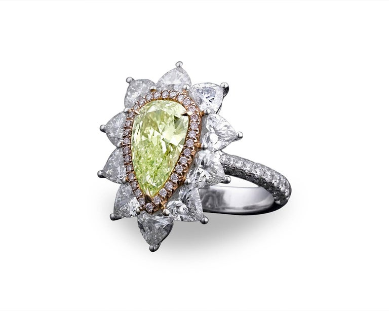 A superb 1.72-carat natural fancy intense yellow-green pear shaped diamond shines in this classic ring crafted of 18K white gold. Ten fiery white pyramid-shaped carat diamonds, weighing 2.48 total carats, beautifully accentuate the rare radiant-cut