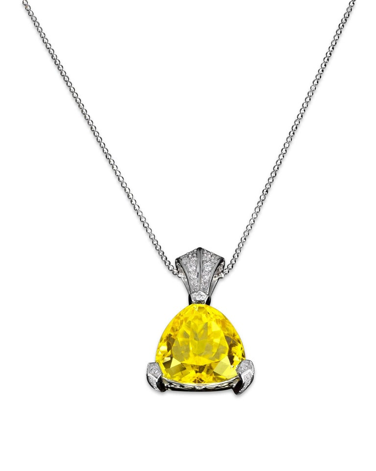 An incredibly rare yellow tourmaline shines with all the brilliance of the sun in this stunning pendant. Weighing an astounding 14.76 carats, this trilliant-cut gem is set with 0.50 carats of white diamonds in its platinum setting.  One of the