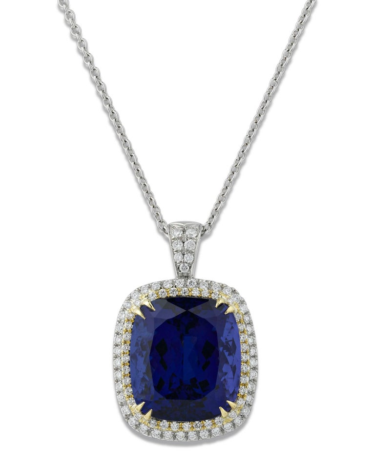 This extraordinary, untreated 24.16-carat tanzanite is truly an extraordinary gemstone. Encircled by 0.99 total carats of shimmering white diamonds, this brilliant cushion-cut gem exhibits the rich violetish-blue color for which these stones are