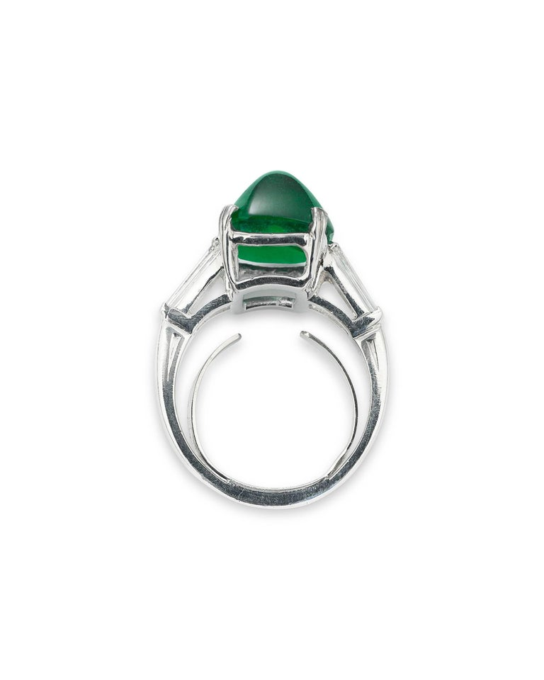 This elegant ring by the renowned Oscar Heyman & Brothers showcases a fantastic sugar loaf emerald. Weighing 7.00 carats, this stunning gem's remarkable cut displays its verdant hue flawlessly. Flanked by two channel-set diamonds weighing .40