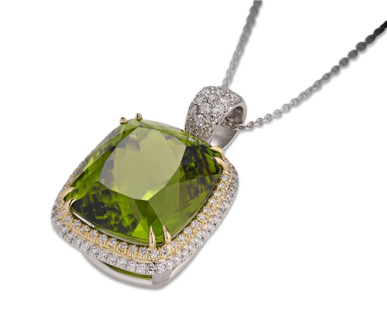 Dramatic in size, yet delicate in color and design, this eye-catching cushion-cut peridot pendant commands attention. Weighing 45.60 dazzling carats, the peridot displays a fresh, green hue that is perfectly accented by 117 diamonds totaling 1.06