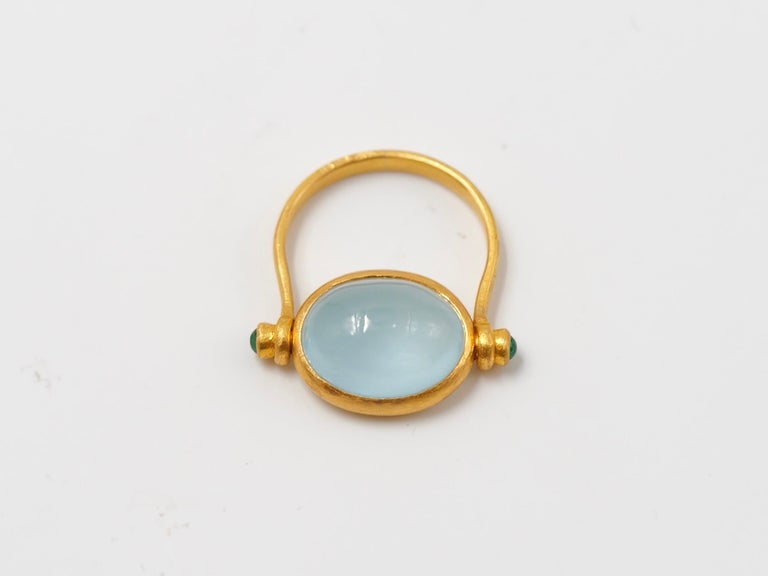 This antique style ring by Scrives is set with a luminous opaque aquamarine cabochon of 5.21 cts and 2 small emerald cabochons (0.15 cts) on the side of the aquamarine.  The central stone and its setting are turning in order to give more comfort.