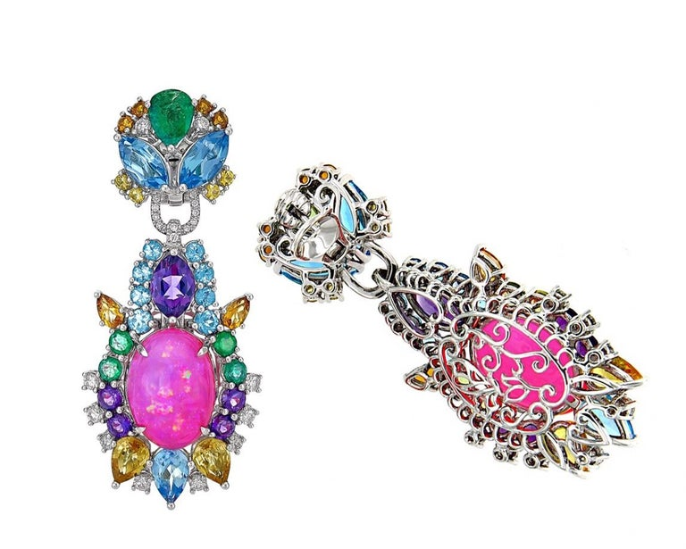 Show stopping hot pink opals weighing 13.38 carats are the centrepiece of these 18k white gold earrings. The pink orbs of pure magnetism are surrounded by hand selected natural coloured gems including, emerald, yellow sapphire, citrine, amethyst and