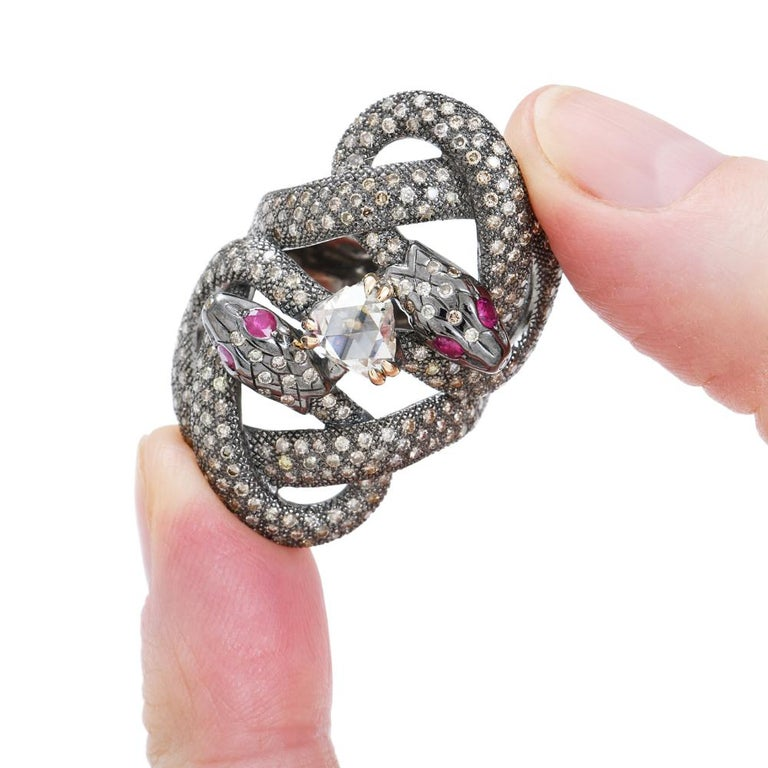 One of a kind double snake ring by Sylvie Corbelin in yellow 750/1000 (18K) gold and patinated silver.  The ring is fully paved with brilliant cut champagne diamonds.  Diamonds weight : 3,70 carats On each eye, a ruby, brilliant cut. Rubies weight :