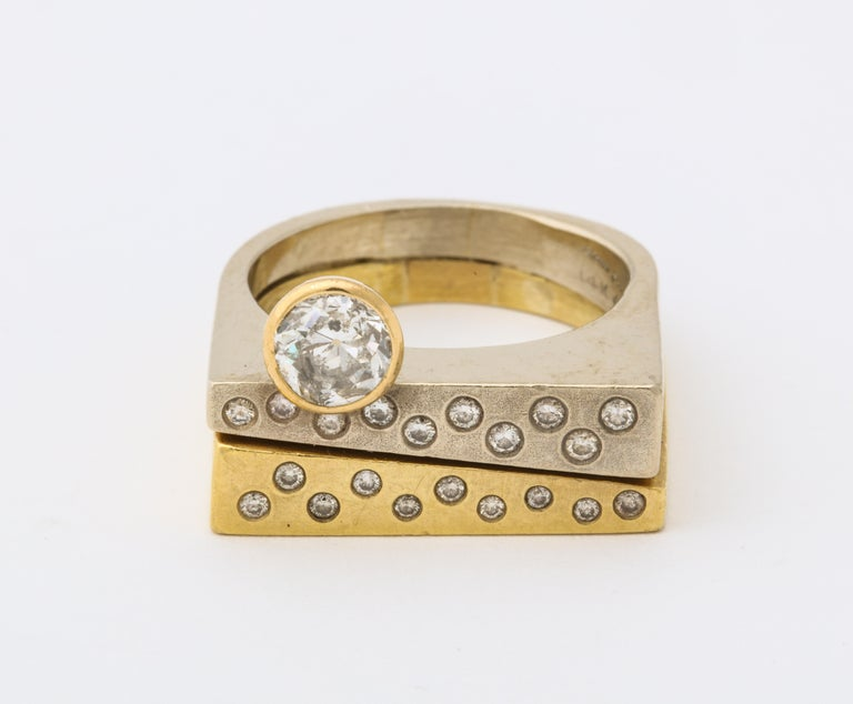 A wonderful modernist two color 18 k gold ring with a brilliant diamond atop of rows of pave diamonds