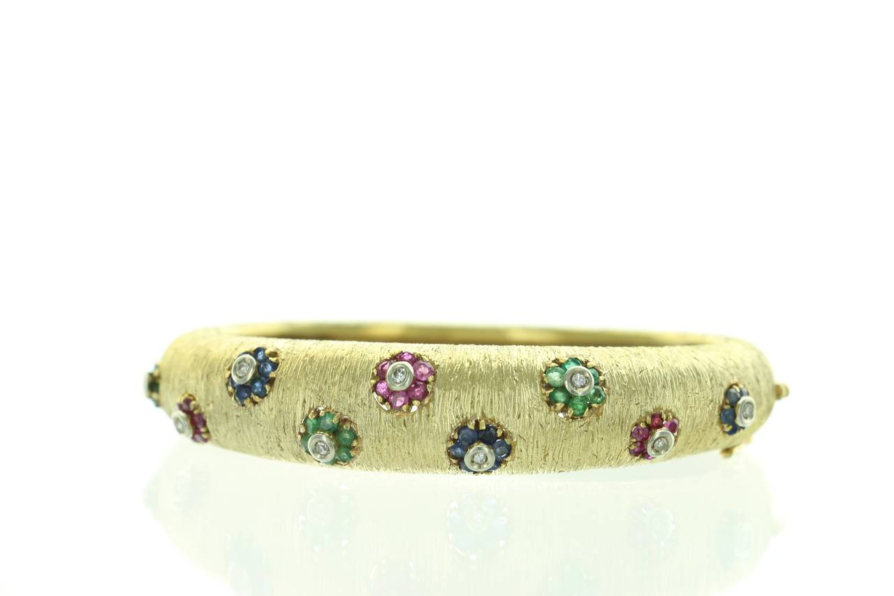 This rare and beautiful, vintage Buccellati bracelet features textured gold finish with ruby, sapphire and emerald flowers, each centered around diamonds. This is truly an elegant piece that shows the craftsmanship and design skills of a legendary