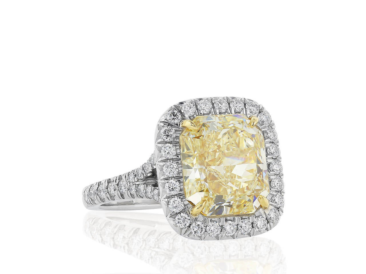 Platinum and 18 karat yellow gold halo ring consisting of 1 radiant cut canary diamond weighing 5.27 carats having a color and clarity of FY/VS2 with GIA certificate 2165655048, the center stone is set with full cut diamond accents.