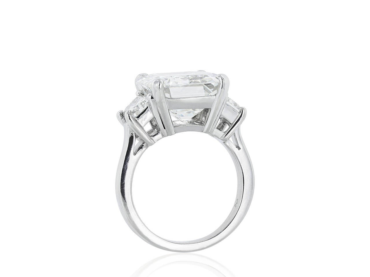 Platinum three stone style engagement ring consisting of one emerald cut diamond weighing 9.01 carats, measuring, having a color and clarity of H/VS1 with GIA report and flanked by two trapezoid cut diamonds, one on each side having a total weight