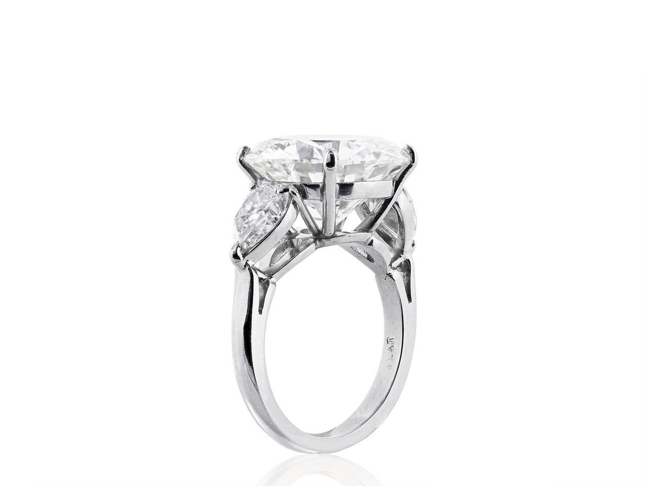 Platinum three stone style engagement ring consisting of one round brilliant cut diamond weighing 9.20 carats, measuring 13.82 - 13.98 x 7.93mm, having a color and clarity of J/VVS2 with GIA report #2165893644 and flanked by two pear cut diamonds,