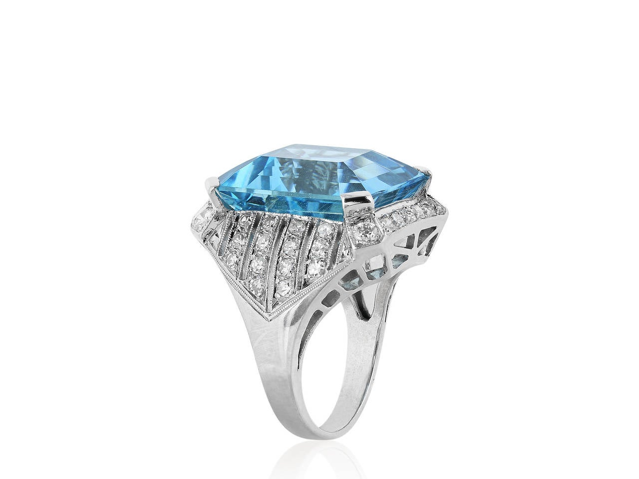 Platinum art deco style ring consisting of 1 emerald cut aquamarine weighing 15.15 carats and accented with pave set rows of diamonds down the shank having an estimated total weight of 1.00 carats.