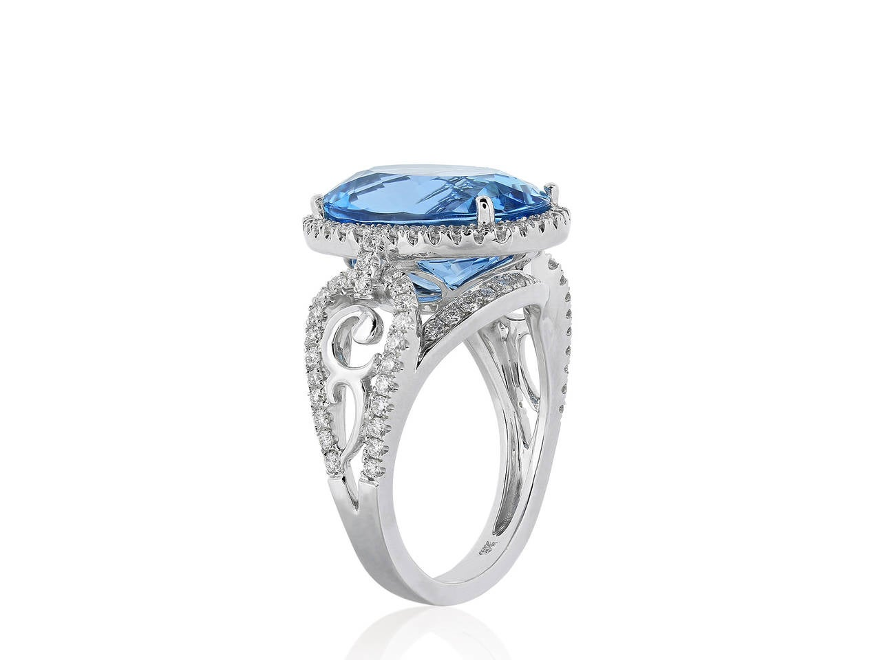 18 karat white gold aquamarine and diamond ring. The ring features 1 oval cut aquamarine having a weight of 6.70 carats. The center stone is surrounded with a halo of full cut diamond and diamond accents on the band having a total weight of .77