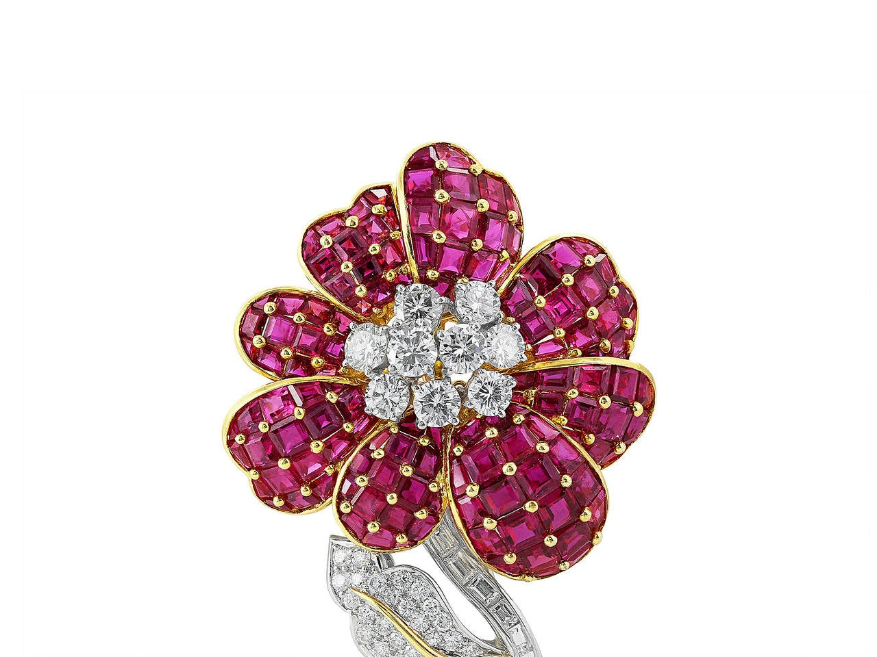 18 karat two tone pin consisting step-cut rubies, featuring 7 round brilliant diamonds in flower design with baguette and round diamonds accenting leaf and stem signed, Oscar Heyman.