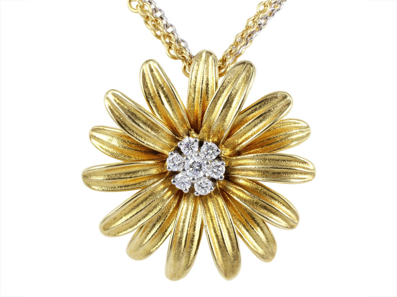 18 karat two tone yellow and white gold dimensional flower pendant by Aaron Henry consisting of 7 full cut round diamonds having a total weight of .28 carats designed in a matte and polished finish and attached to a triple strand 16 inch cable link