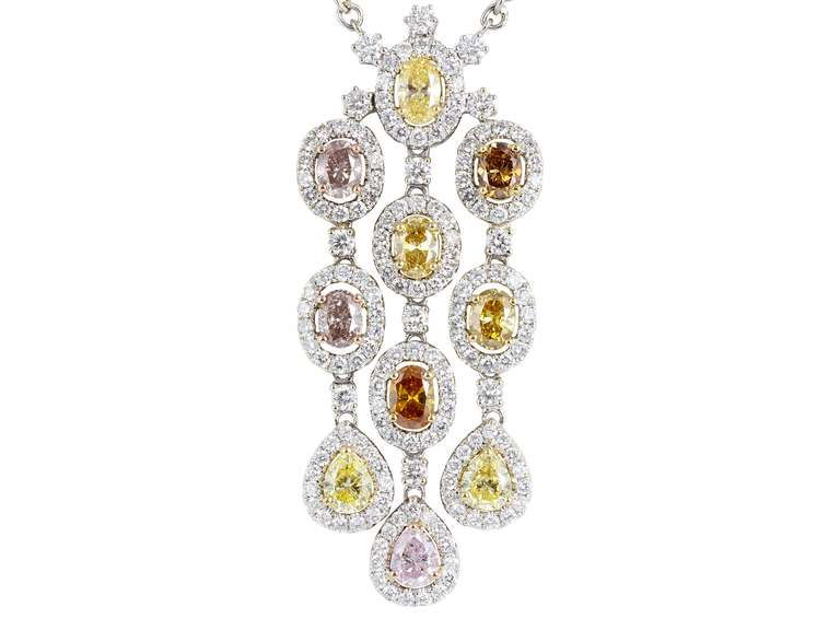 18 karat white gold drop pendant consisting of 10 oval and pear shaped natural multi color diamonds having a total weight of 2.68 carats set with 2.25 carats total weight of colorless round brilliant cut diamonds.