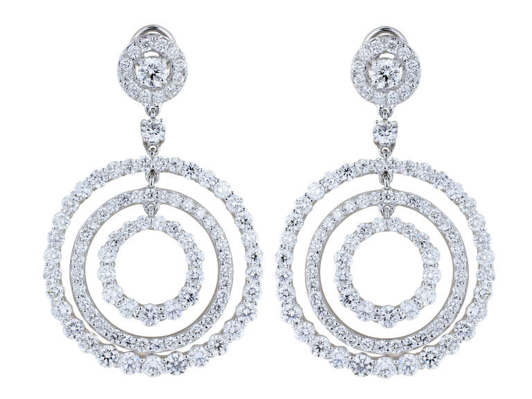 Platinum drop triple hoop earrings consisting of 11.11 carats total weight of round brilliant cut diamonds having a color and clarity of G/VS1 respenctively