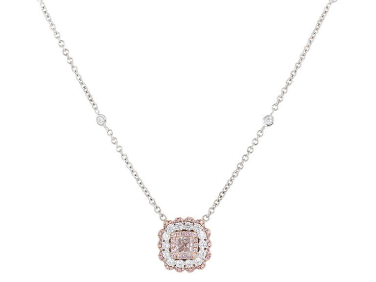 Two tone 18 karat white and pink gold pendant consisting of 1 radiant cut natural pink diamond weighing .85 carats set with 1.20 carats total weight of colorless round brilliant cut diamonds and .45 carats total weight of natural pink round
