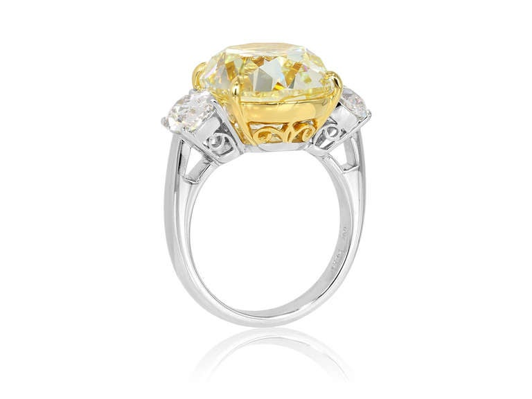 Platinum and 18 karat yellow gold, custom made, three stone style ring consisting of 1 antique cushion cut diamond weighing 10.79 carats, having a color and clarity of FY/SI1, measuring 13.94 x 12.48 x 7.99mm with GIA certificate #2155280366 and