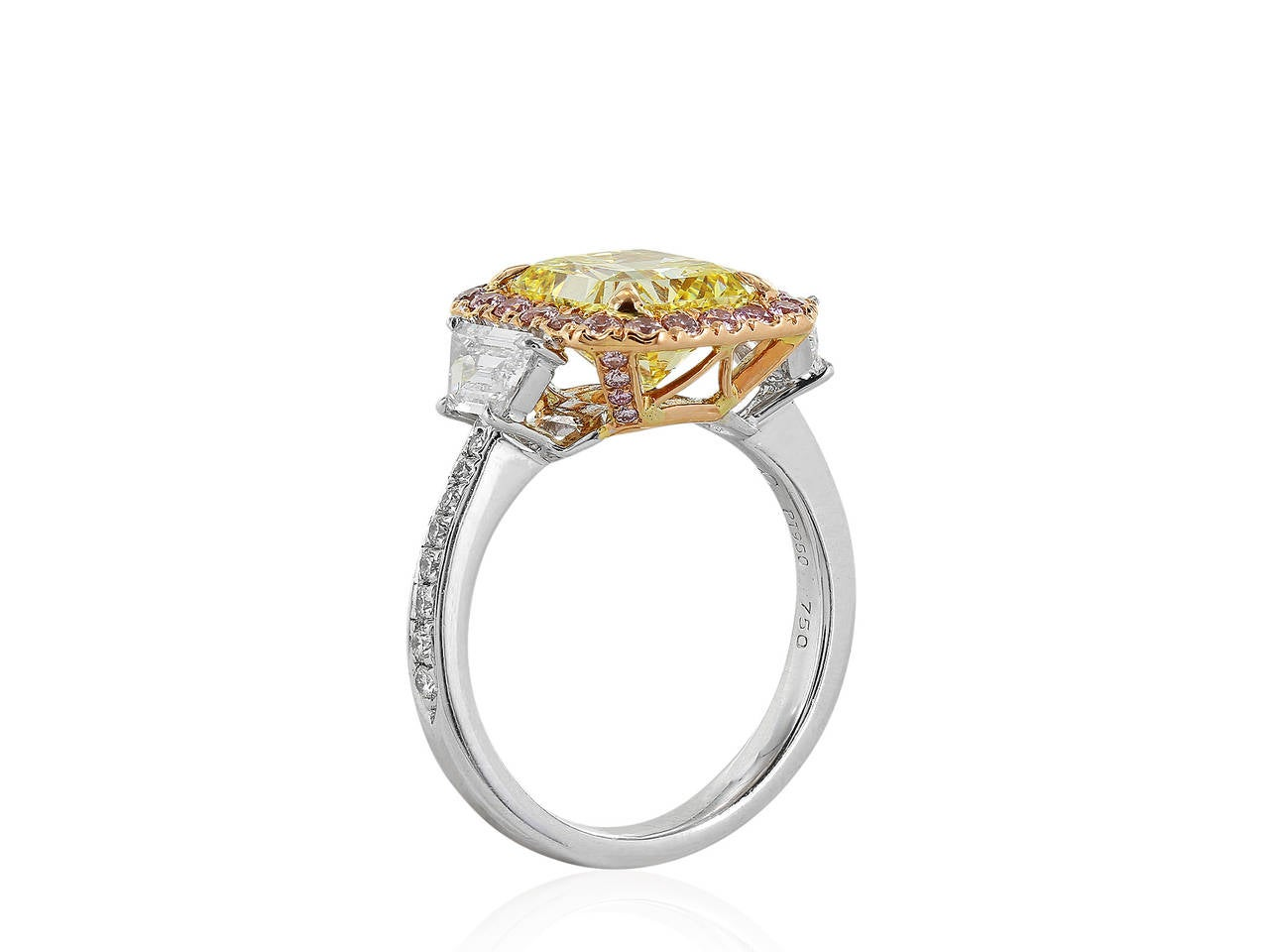 Stunning platinum and 18 karat pink gold 3 stone halo ring consisting of 1 radiant cut natural canary diamond weighing 3.02 carats having a color and clarity of FIY/VS1 with GIA certificate #15876346, the center stone is flanked by 2 colorless step
