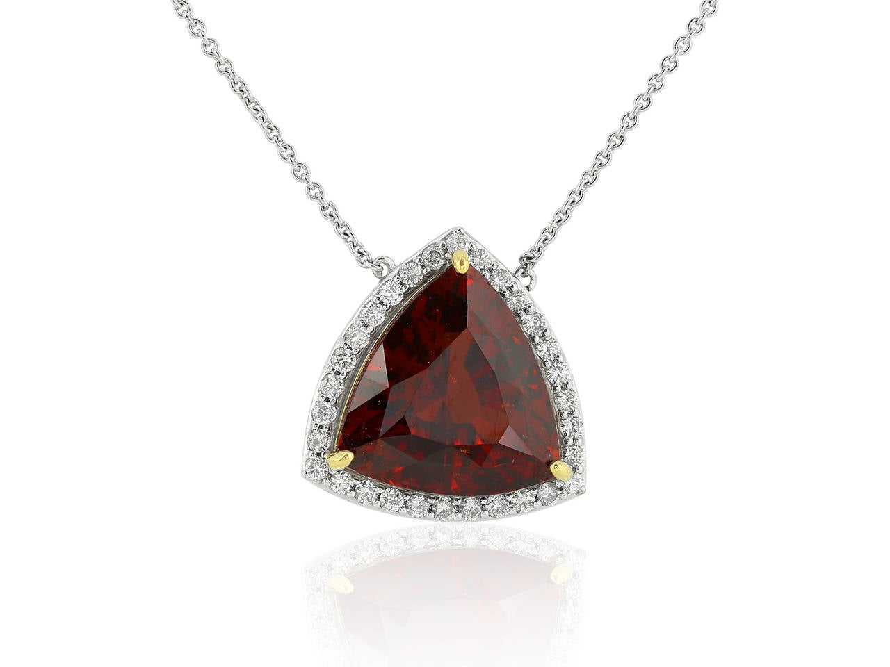 14 karat white gold pendant consisting of one trilliant shape Almandine Garnet weighing approximately 12.75 carats surrounded by 1 row of round brilliant cut diamond accents.