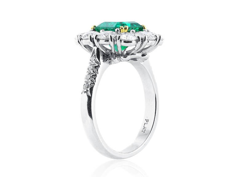 Elegant and Sophisticated platinum cluster ring set with a fine gem quality 2.16 carat Colombian Emerald center stone with AGL certificate CS 61146, the center stone is surrounded by 10 full cut round brilliant diamonds totaling approximately 2.00