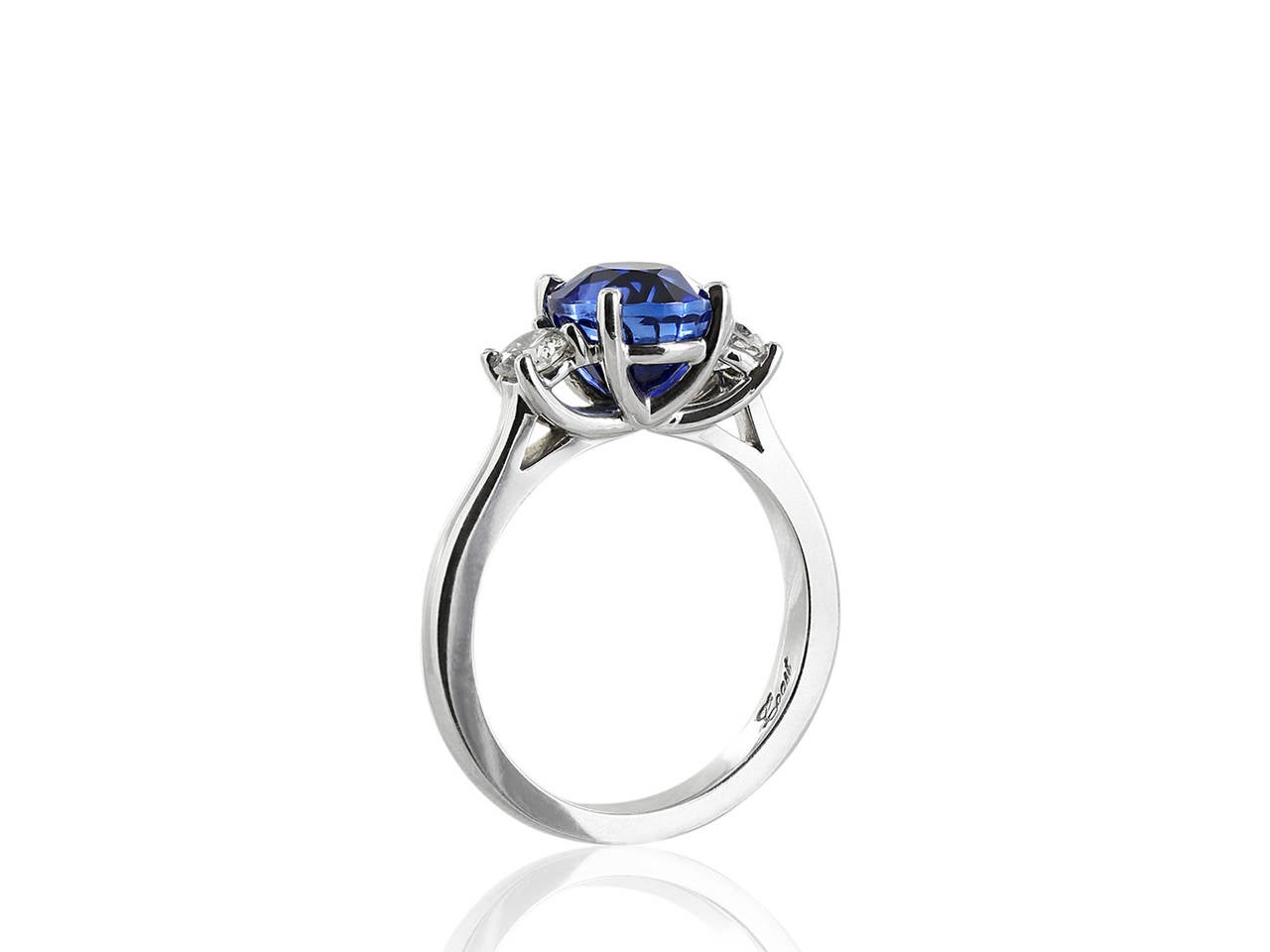 18 karat white gold 3 stone ring consisting of 1 round brilliant sapphire weighing 3.01 carats, the center stone is flanked by two round brilliant diamonds having a total weight .37 carats.