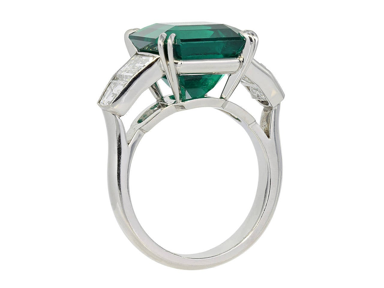 Platinum custom made 5 stone ring consisting of 1 square emerald cut Colombian emerald weighing 7.28 carats with GIA certificate #5111867580, the center stone is flanked by 2 step but half moons weighing .80 carats and 2 step cut trapezoid shaped