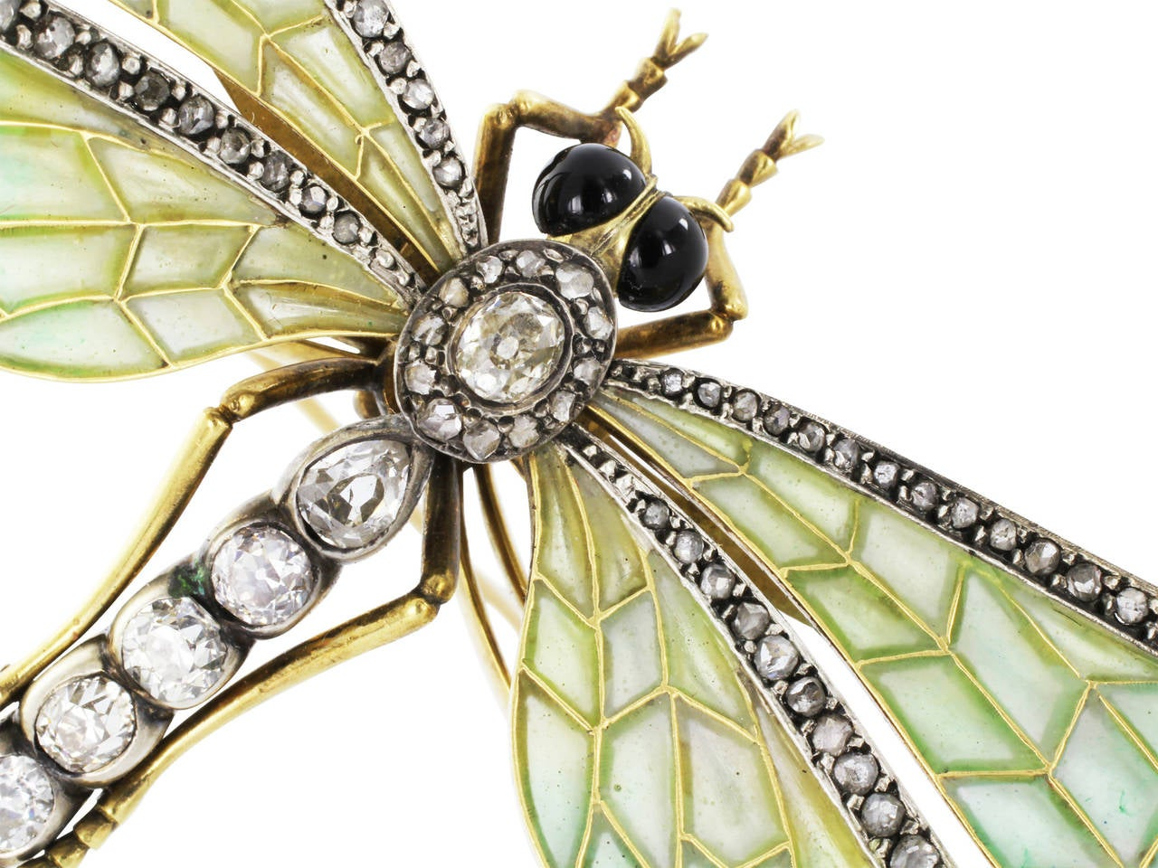 Sterling silver on 18 karat yellow gold antique dragonfly pin with blue - green plique-a-jour wings and antique cut diamond accents in the torso and on the wings and black onyx eyes.