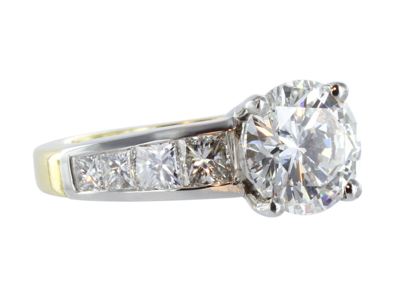 Platinum and 18 karat yellow gold ring consisting of one GIA certified round brilliant cut diamond weighing 2.26 carats, with a color of G and a clarity of VS2. The center stone is flanked by 8 channel set princess cut diamonds, 4 on each side