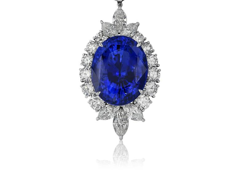 Platinum custom made cluster style enhancer and necklace. The removable enhancer consists of 1 oval shaped blue sapphire weighing 50.14 carats with AGL certificate CS 83481 stating Ceylon origin, surrounded by 6 marquise cut diamonds having a total