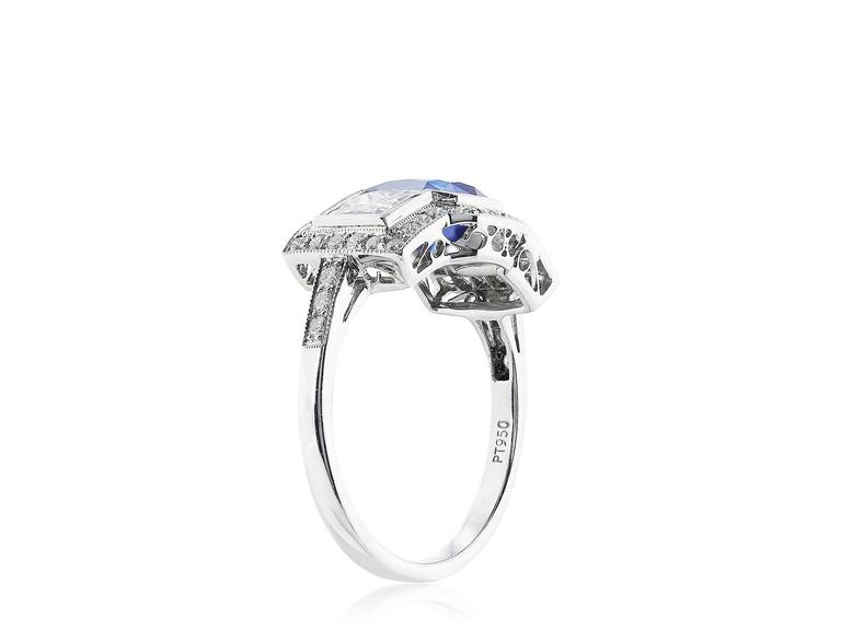 Platinum vintage style 3 stone ring. Consisting of one square cut sapphire weighing 1.73 carats flanked by 2 square cut diamonds having a total weight of 1.09 carats, the 3 stone are surrounded by 1 row of full cut diamonds having a total weight of