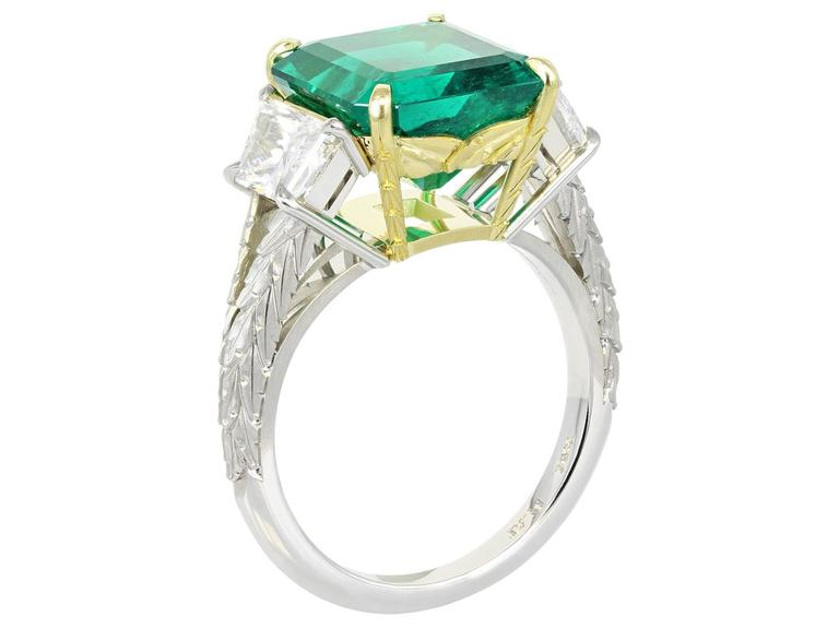 Platinum and 18 karat yellow gold custom made 3 stone ring consisting of 1 square emerald cut Colombian emerald weighing 5.00 carats, measuring 10.94 x 10.03 x 6.49mm the center stone is flanked by 2 brilliant cut trapezoid diamonds having a total