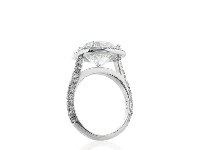 Platinum custom made ring consisting of 1 round brilliant diamond weighing 5.02 with a color and clarity of J/SI1 respectively, with GIA cert 6167549610 surrounded by full cut round diamonds and extending down the sides.