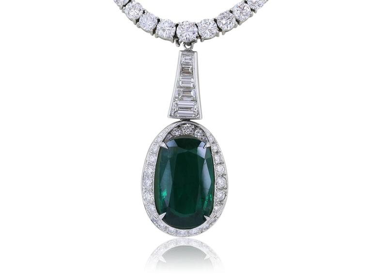 Platinum graduated Riviera diamond necklace, consisting of approximately 12 carats total weight of prong set full cut diamonds, 133 round diamonds and 1 marquis cut diamond on the clasp, featuring a detachable 8.09 carat cushion cut Emerald drop