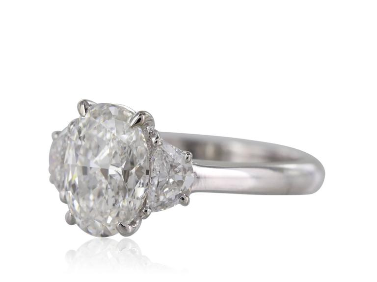 18 karat white gold Oval Diamond ring weighing 2.01 carats GIA G SI2 flanked by pair of half moon diamonds weighing .59 carats.Shreve, Crump & Low