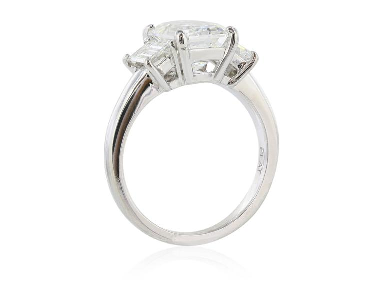 Platinum set custom made three stone diamond ring featuring one GIA certified emerald cut center stone weighing 3.01 carats with a color of G and a clarity of VS2.  The center diamond is flanked by two emerald cut sides stones, each with a color of
